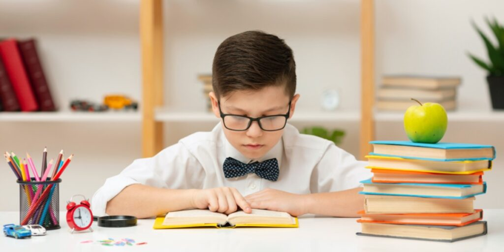 A picture of a young boy with a bow tie and glasses concentrating on reading a book to represent reading a scientific paper effectively