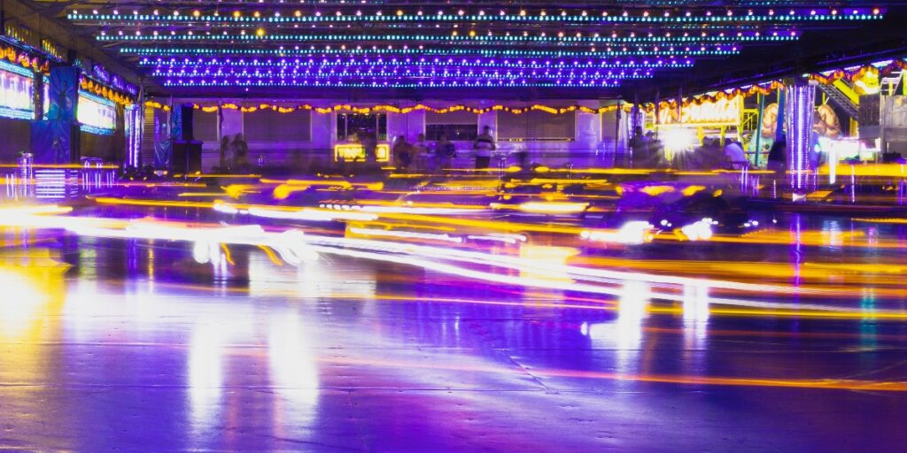 A picture of dodgems at a fairground surrounded by blurred fast light to represent speed reading