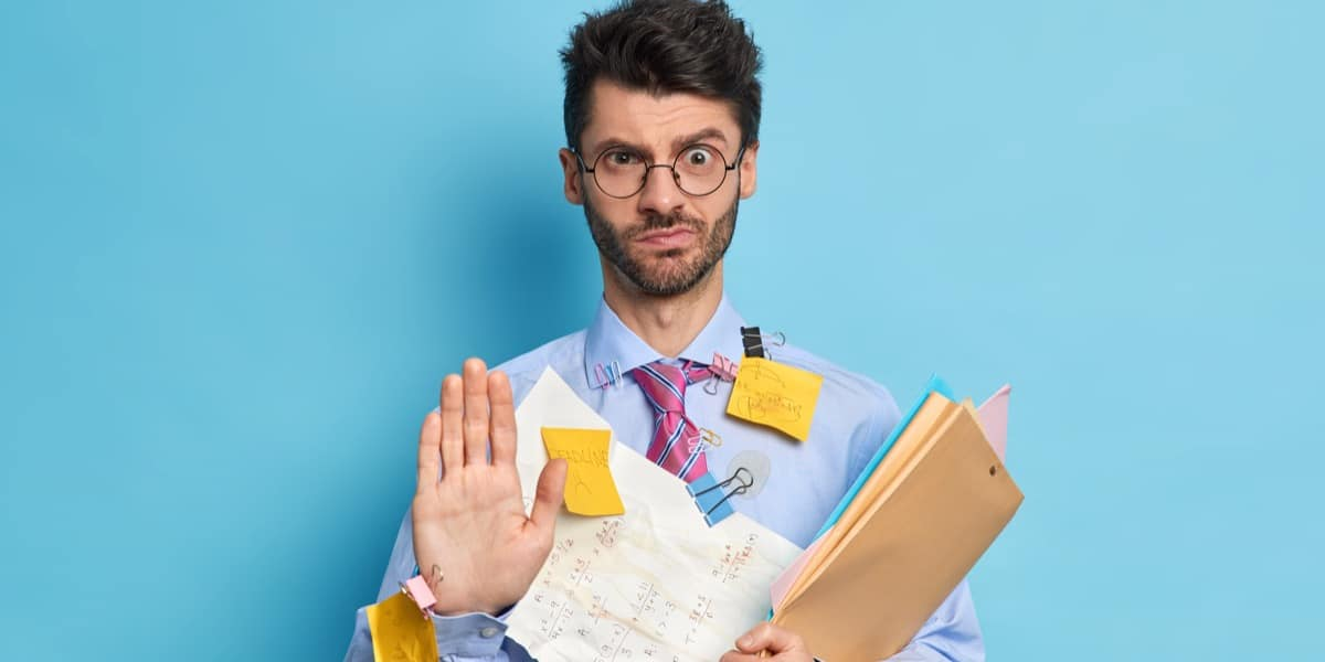 A bearded man dressed formally holding various documents and covered in sticky notes to represent getting started with reference managers for scientists