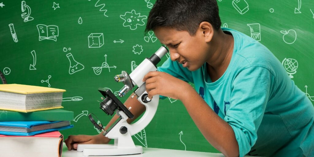 Image of a child looking puzzled at a microscope to represent uncertainty as to what histology fixatives are doing to samples.