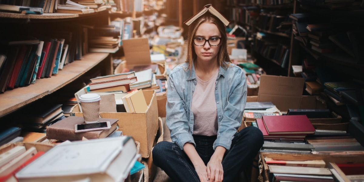 A young woman sitting on the floor of a library aisle surrounded by books and coffee and with an open book balanced on her head to represent keeping up with the literature