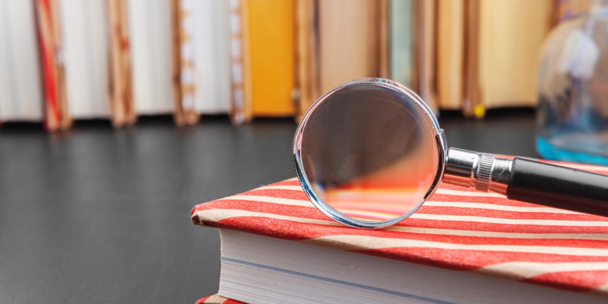 Magnifying glass on a book, symbolizing how a DOI allows doucments to be found