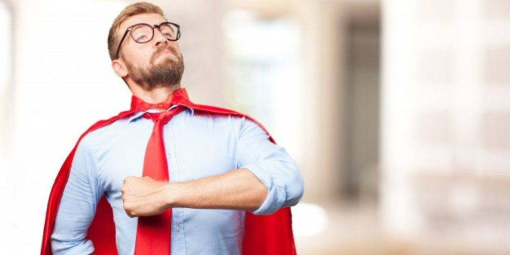 A man with a red tie and red cape standing proudly.