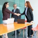Two smiling women shaking hands and one smiling man standing in an interview room to represent getting a job after reading how to make a great impression at your life sciences interview