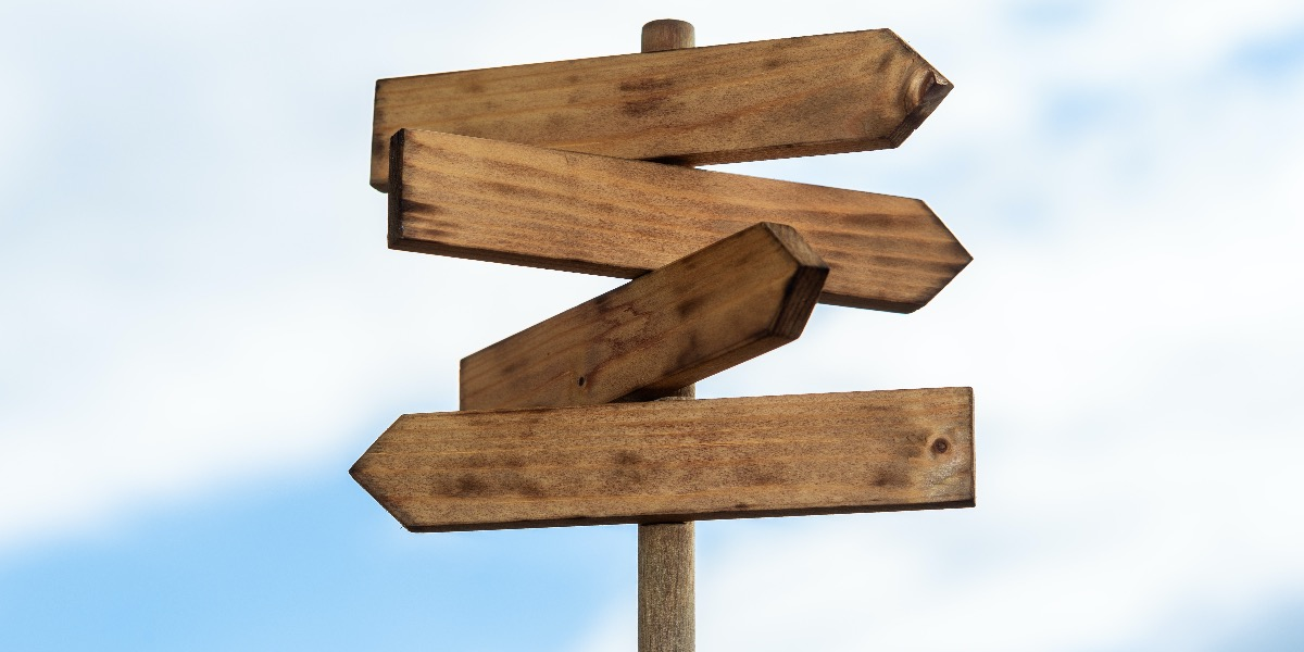 Picture of four empty wooden signs pointing in different directions to represent different life sciences career paths