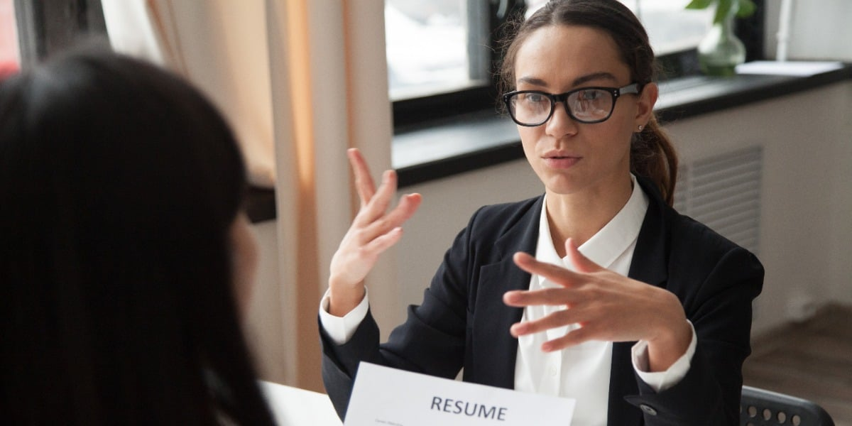 A confident female candidate discusses her resume and research interest statement at a job interview.