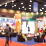A blurred photograph of an event exhibition to represent a scientific conference and someone presenting a scientific research poster