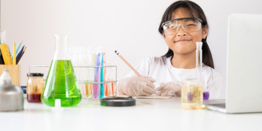 A photo of a young girl wearing lab coat and safety glasses surrounded by chemistry apparatus and writing in a book to represent organizing your lab book
