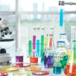 Lab bench with microscope and lots of different coloured reagents in flasks and test tubes to represent someone performing successful experiments