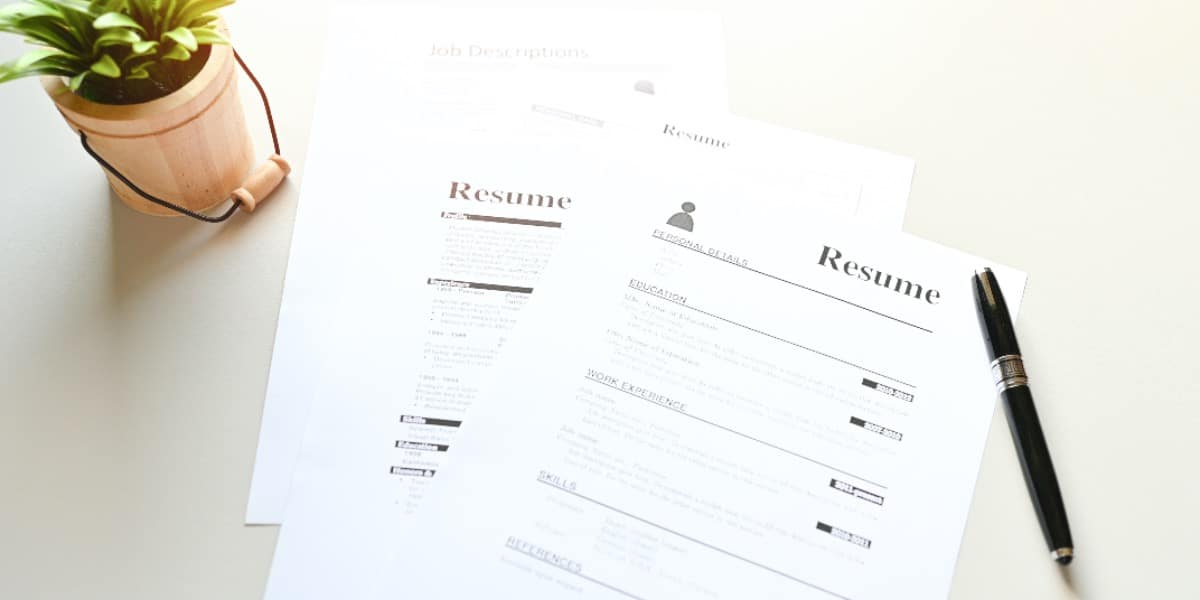 Resume and pen on a table to represent someone applying for alternative careers for scientists