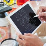 A picture of a scientist's hands holding a tablet with scientific notations surrounded by a microscope and scientific equipment to represent someone with a career in bioinformatics