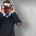 A picture of a man holding binoculars with a surprised expression to represent learning how to improve your PubMed searches
