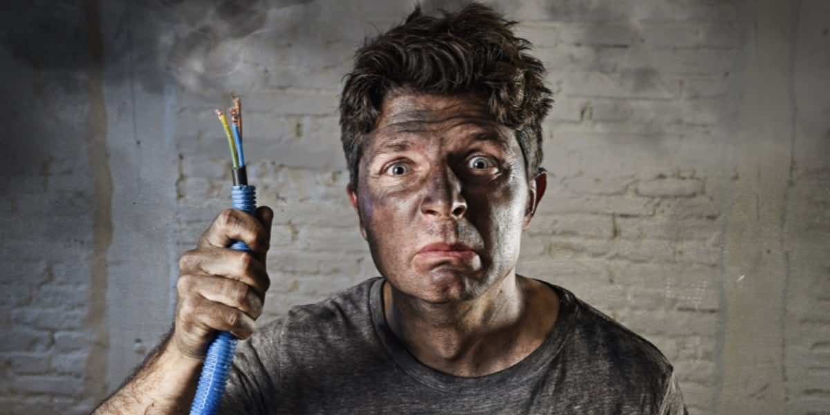 Picture of an unhappy looking man covered in soot and holding a cable with exposed wires to represent choosing between constant current or voltage in SDS-PAGE