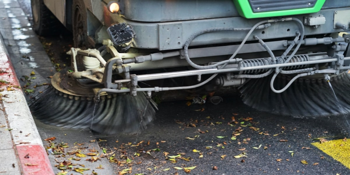 A street sweeper sweeping leaves from a road to represent DNA clean-up