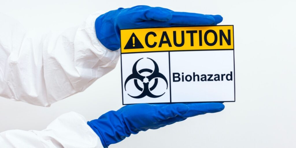 An image of a person's arms in a hazmat suit holding a biohazard warning sign to represent common lab safety signs
