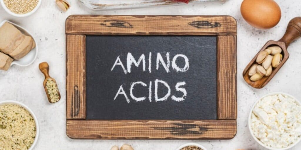 Image of chalkboard with the words amino acids surrounded by health foods to juxtapose the topic of unnatural amino acids