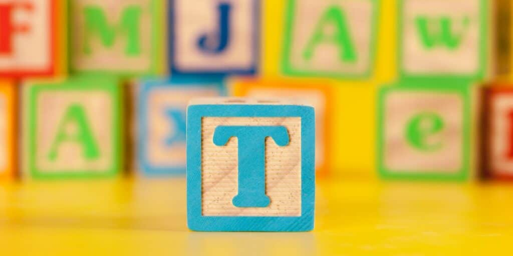 A wooden block with a letter t in front of several other blurred wooden blocks to represent the 3 Ts of introducing foreign DNA