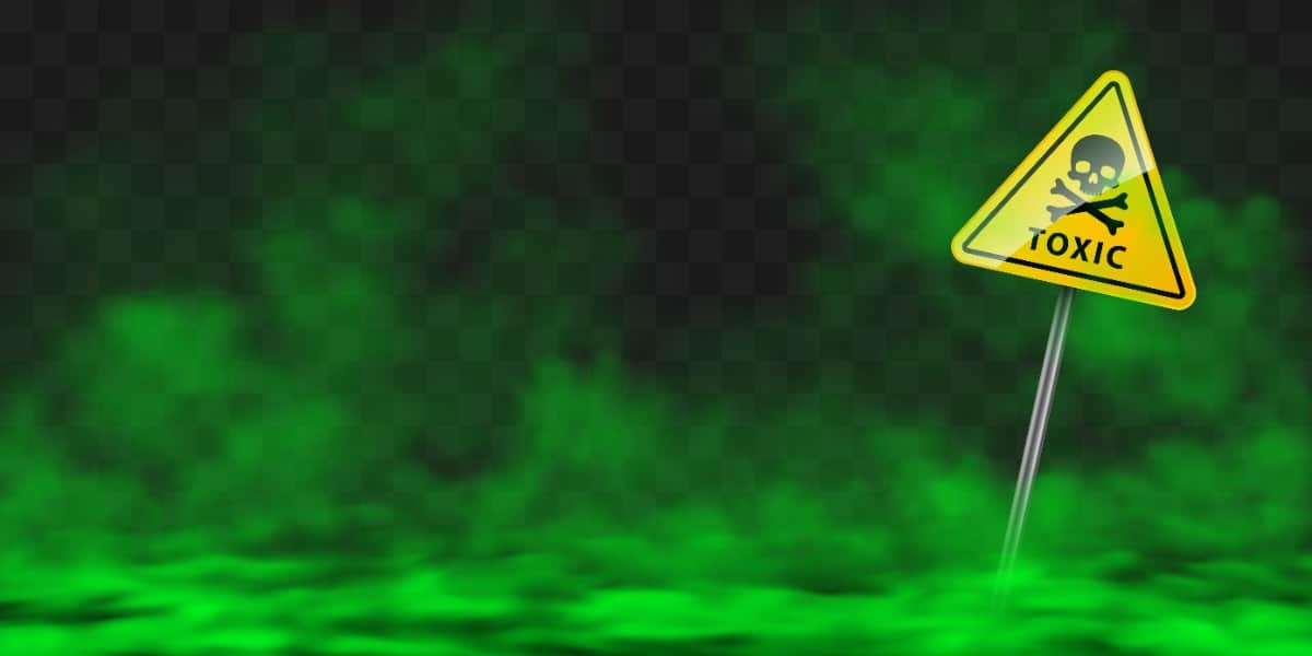 An image of green smoke and a toxic warning sign to depict 10 dangerous chemicals in the lab.