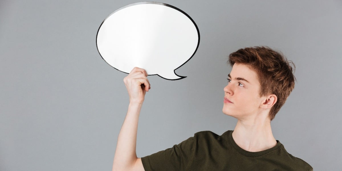 Image of a man holding up a speech bubble to indicate thesis writing tips like how to insert captions and a table of contents in Word