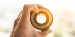 Man holding a lens up to the light to represent lenses and objectives